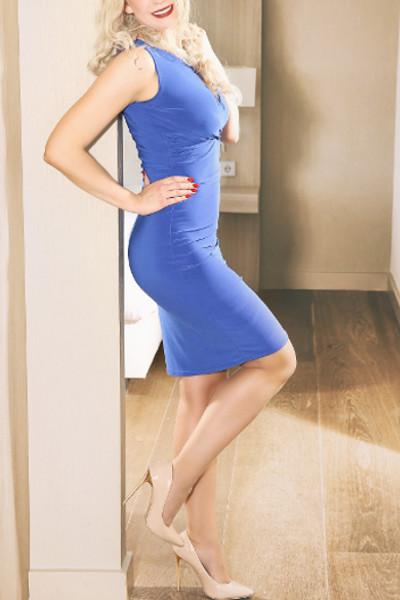 Valerie - Escort Model Stuttgart besticht im blauen Kleid mit beigen Strümpfen.