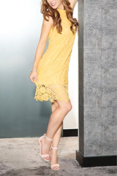 Fiona Escort Köln im gelben Kleid mit Sandalen an der Wand.