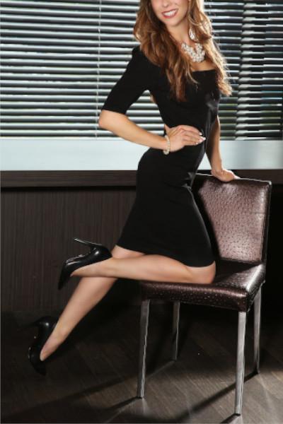 Escort Model Köln Fiona im schwarzen Kleid mit schwarzen Schuhen auf einem Stuhl.