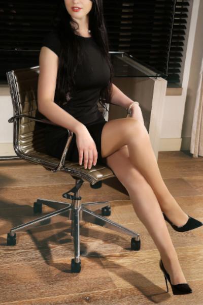 Alcina - Escort Model Saarbrücken im schwarzen Kleid am Schreibtisch sitzend.