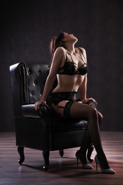Emilia - Escort Model Krefeld mit schwarzer Wäsche auf einem Sessel.