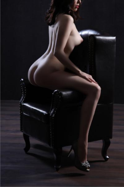 Emilia - Escort Model Krefeld nackt auf einem Sessel mit High Heels.