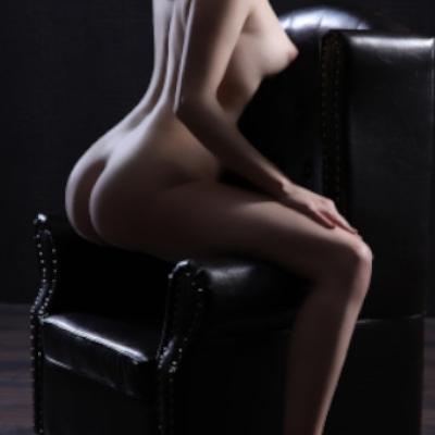 Emilia - Escort Model Krefeld nackt auf einem schwazen Sessel mit Ansicht von Hinten