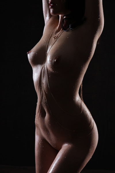 Emilia - Escort Model Krefeld nackt mit einer Körperkette und dunklem Hintergrund.