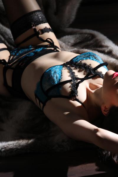 Emilia - Escort Model Krefeld auf dem Rücken liegend mit blauer Wäsche und schwarzen Strümpfen.