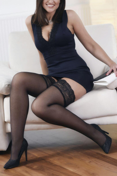 Escort Model Geraldine aus Frankurt im kurzen schwarzen Kleid sitzend auf einem Sessel.
