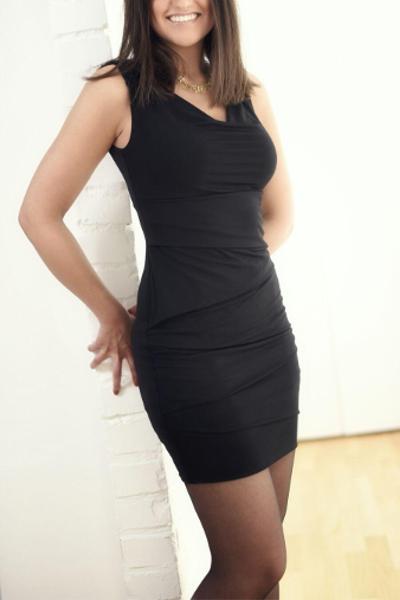 Escort Model Geraldine aus Frankurt im schwarzen Kleid an einer Wand lehnend.
