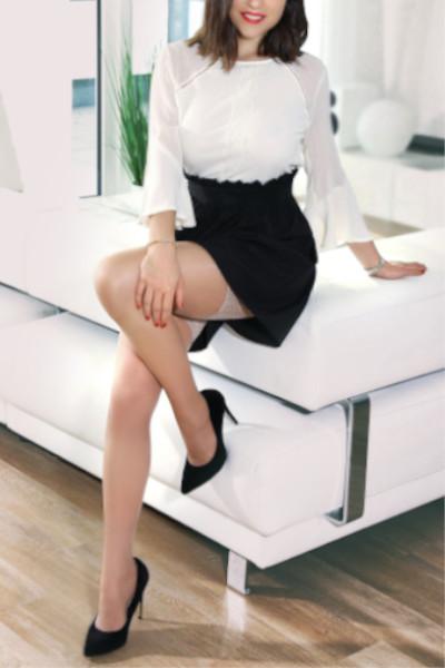Ines - Escort Model Stuttgart im Business Dress auf dem Sofa sitzend.