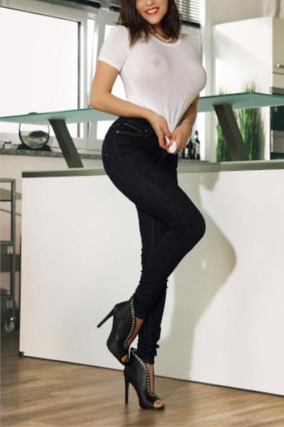Ines - Escort Model Stuttgart in Jeans und einem weissen durchsichtigen Oberteil.