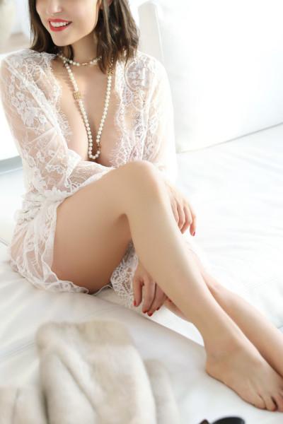 Ines - Escort Model Stuttgart lächelnd auf dem weissen Sofa mit offenem Morgenmantel