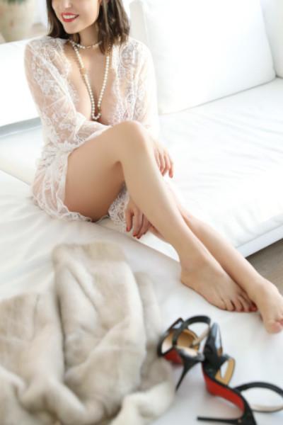 Ines - Escort Model Stuttgart sitzend mit Perlen und einem offenen Morgenmantel