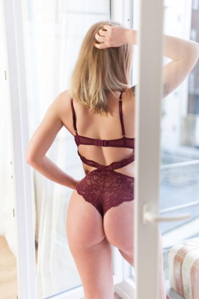 Charlotte Escort Lady Essen im roten Body von Hinten am Fenster.