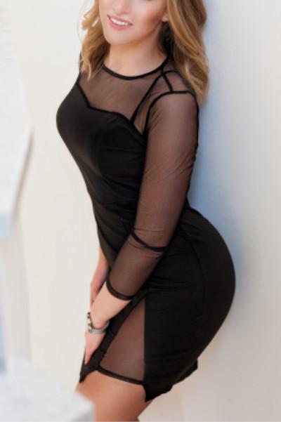 Charlotte Escort Lady Essen mit einem kleinen schwarzen Kleid lehnend an der Wand.