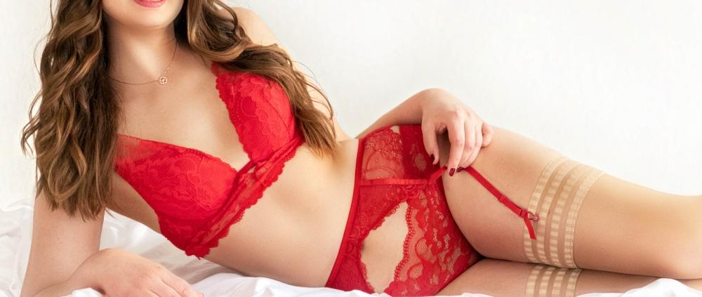 Laura - Elite Escort Model Essen mit roten Dessous auf der Seite liegend.