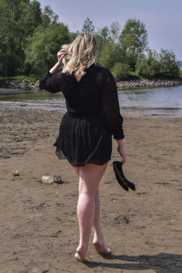 Annika - Escort Model Köln am Strand von hinten im schwarzen Kleid.