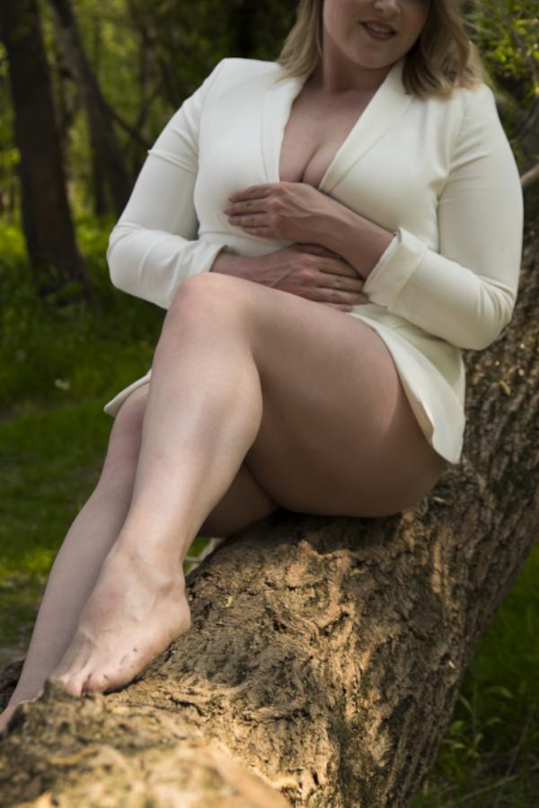 Annika - Escort Model Köln auf einem Baum mit weissem Blazer.