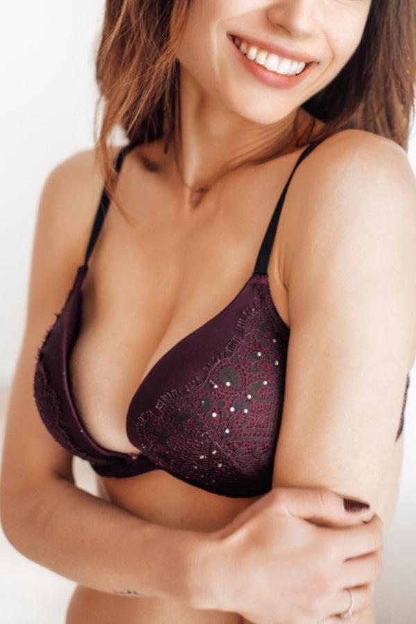 Laureen - Escort Model Heidelberg lächelnd mit roten Dessous.