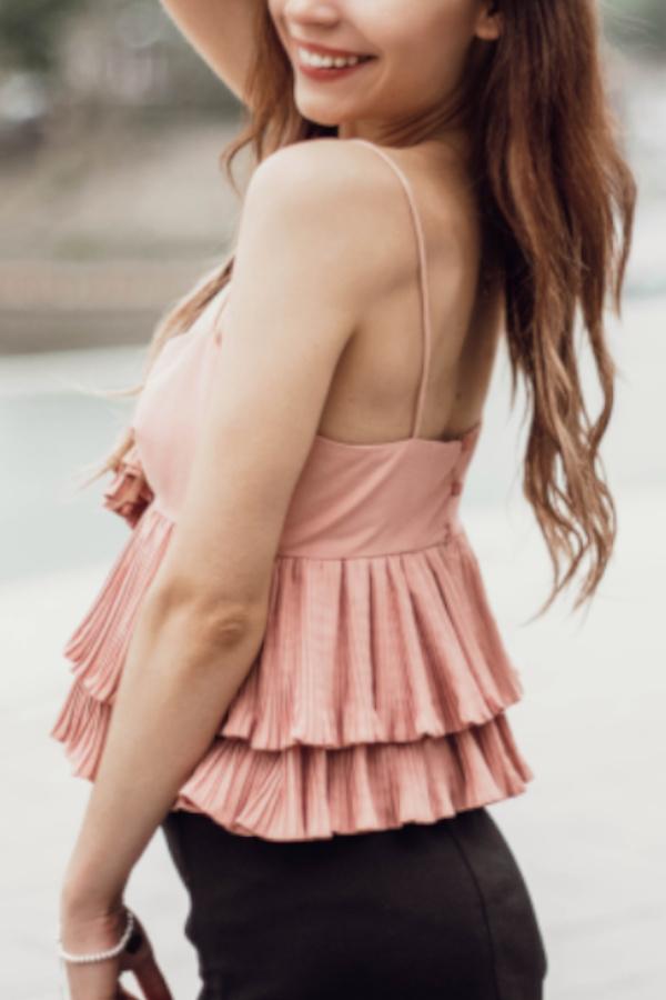 Laureen - Escort Model Heidelberg lächelnd mit einem rosa Top.