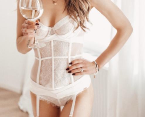 Laureen - Escort Model Heidelberg mit einer weissen Korsage und einem Glas Wein in der Hand.