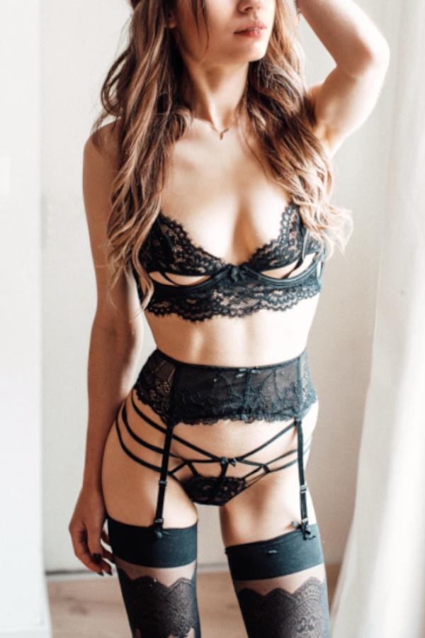 Laureen - Escort Model Heidelberg mit schwarzer Wäsche und langen lockigen Haaren.