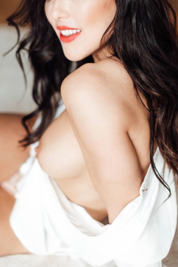 Sarina - Escort Model Düsseldorf lachend über die Schulter.