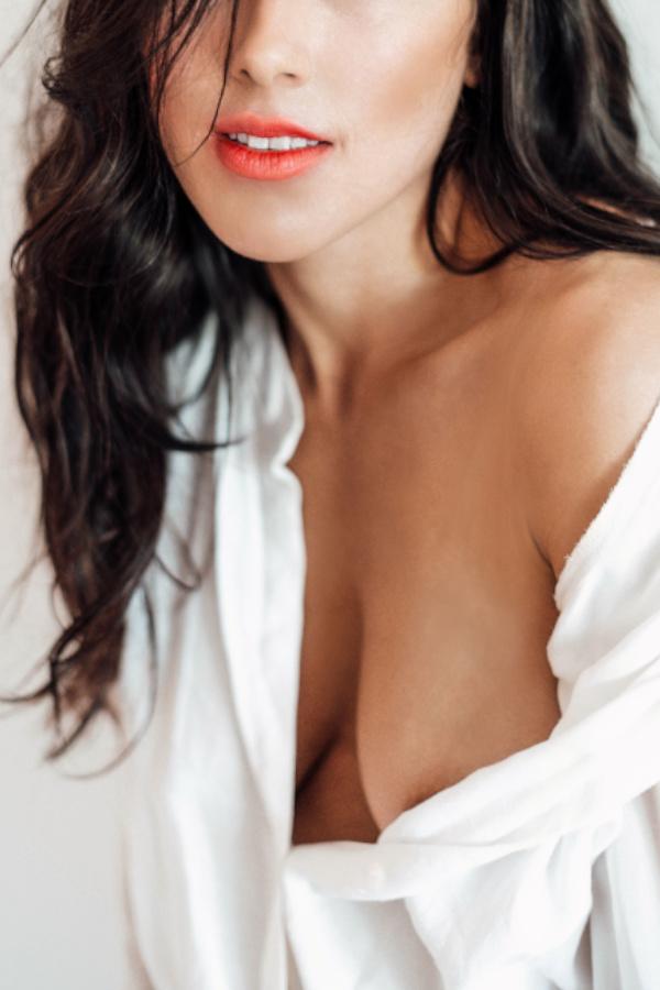 Sarina - Escort Model Düsseldorf lächelnd, mit roten Lippen und einer weissen Bluse.