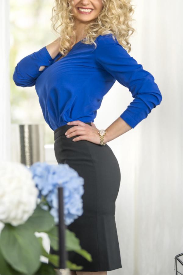 Angelina - Escort Model Dortmund mit blauer Bluse hinter Blumen.