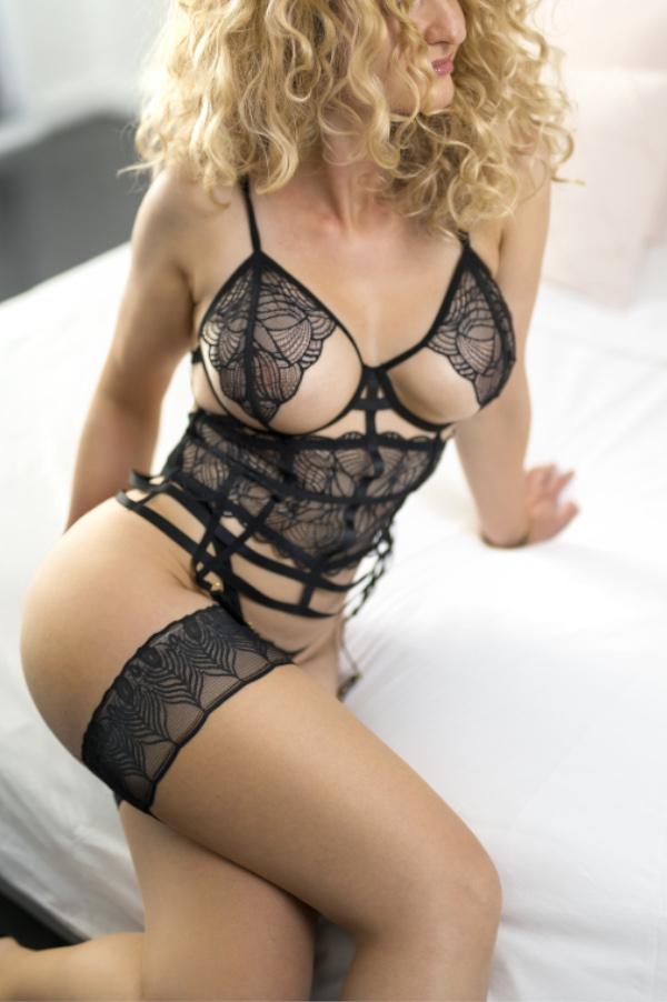 Angelina - Escort Model Dortmund seitlich auf einem weissen Bett sitzend.