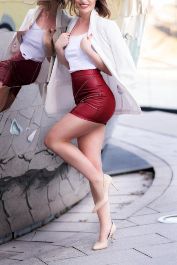 Frankfurt Escort Model Gisele im roten Lederrock vor einer Skulptur stehend.