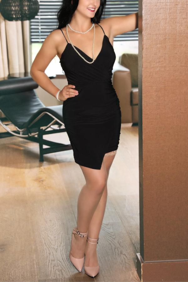 Escort Model Gloria aus Kassel im schwarzen Kleid an der Wand lehnend.