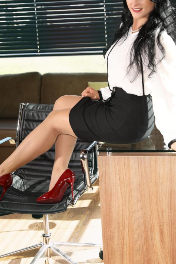 Escort Model Gloria aus Kassel im Business Outfit am Schreibtisch.