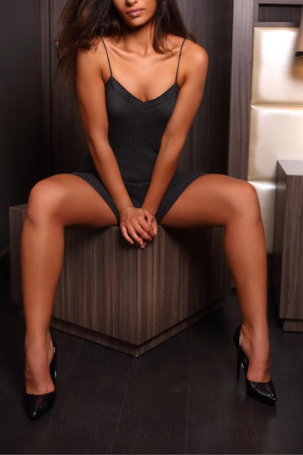 Jana - Escort Model NRW auf einem Tisch sitzend mit gespreizten Beinen.