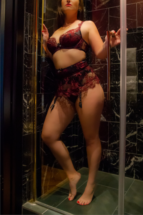 Escort Berlin Model Jasmin in einer dunkel gekachelten Dusche.
