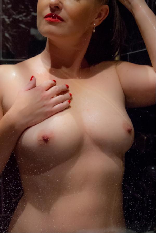 Escort Berlin Model Jasmin unter der Dusche mit roten Nägeln.