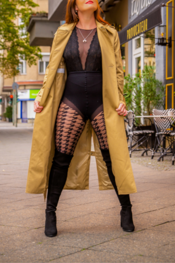 Escort Berlin Model Jasmin im biegen Trencoat auf der Strasse stehend.