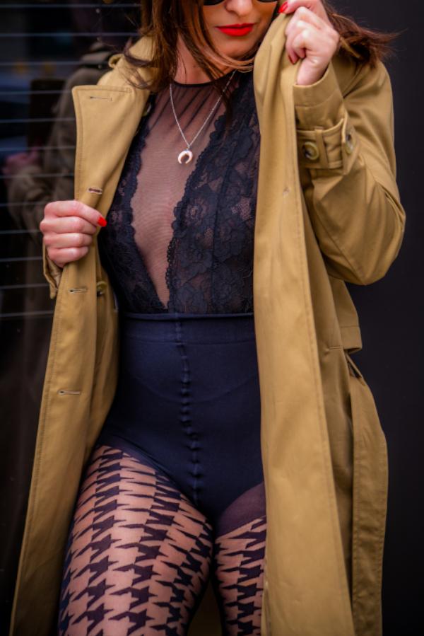 Escort Berlin Model Jasmin im schwarzen Body und einem beigen Trenchcoat.