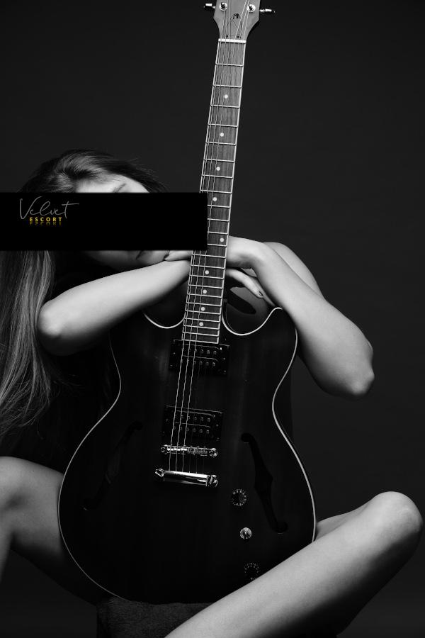 Josepine - VIP Escortdame Hannover nackt hinter einer Gitarre.