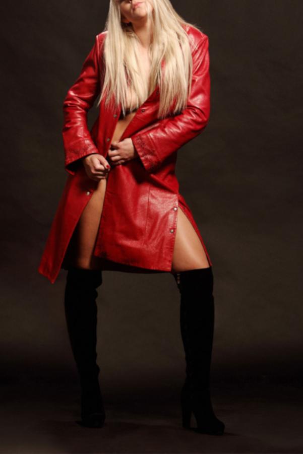 Valerie - Escort Model Stuttgart mit schwarzen Stiefeln und einem roten Mantel.