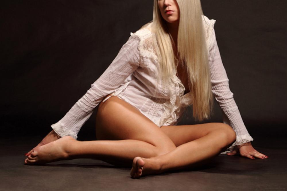 Valerie - Escort Model Stuttgart mit einer weissen Bluse auf dem Boden sitzend.