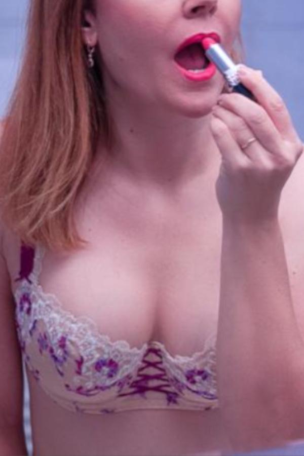 Nicole - Elite Escort München vor dem Spiegel mit rosa-weissen Dessous