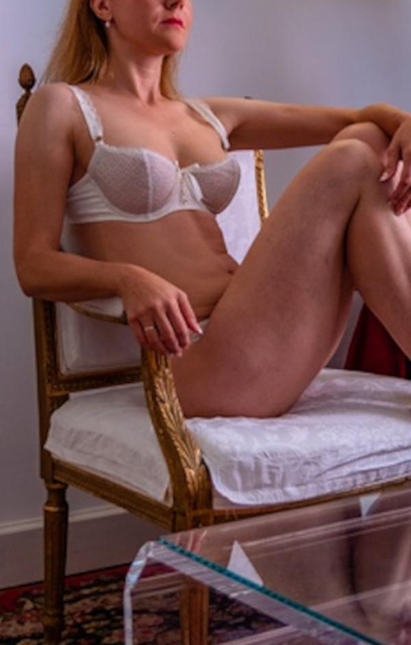 Nicole - Elite Escort München in weissen Dessous auf einem Stuhl sitzend