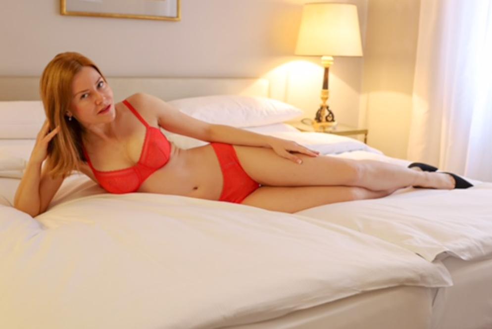 Nicole - Elite Escort München mit roten Dessous seitlich auf dem Bett liegend.