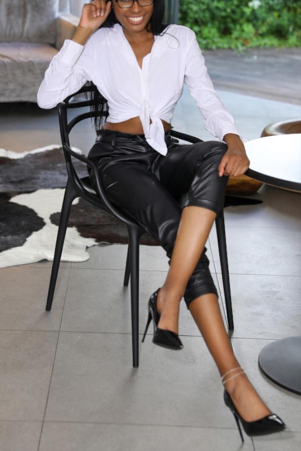 Emy - Escort Model Frankfurt in Bluse und Business Hose auf einem Stuhl sitzend.