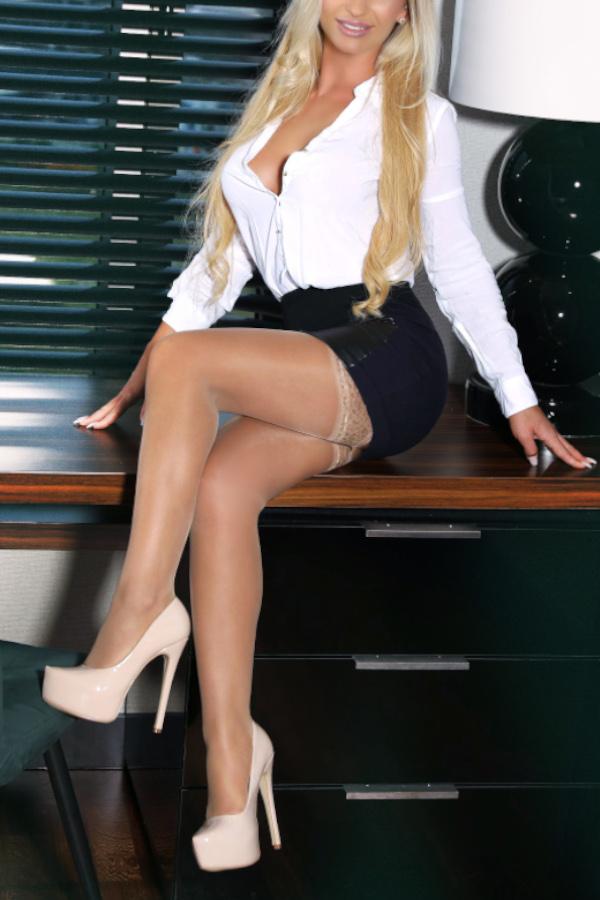 Alyssa - Escort Model Frankfurt im Business Outfit auf einem Tisch sitzend.