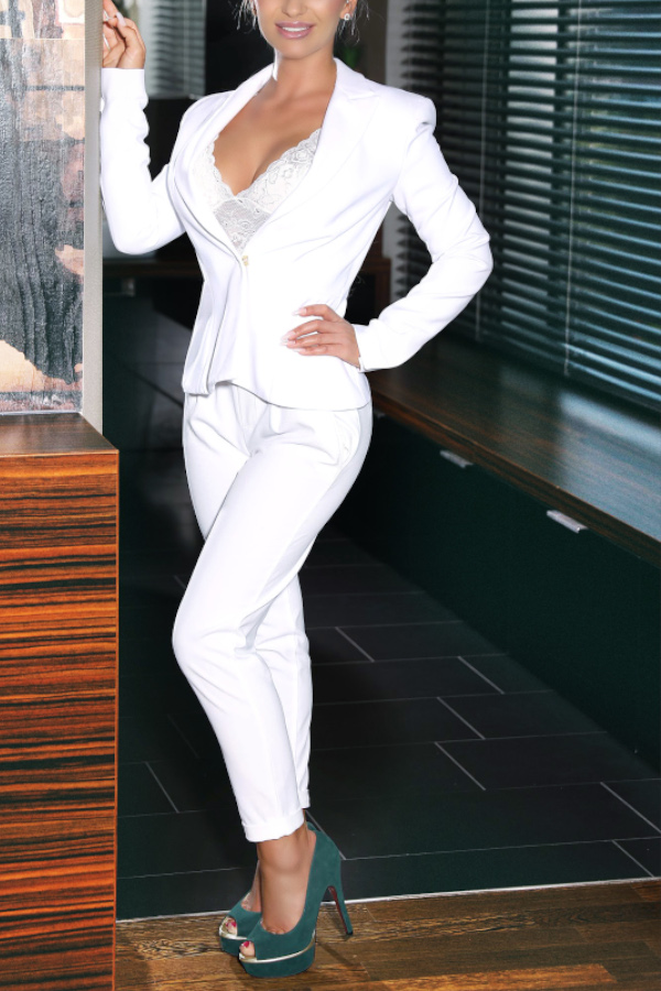 Alyssa - Escort Model Frankfurt in weisser Hose und Blazer im Badezimmer stehend.