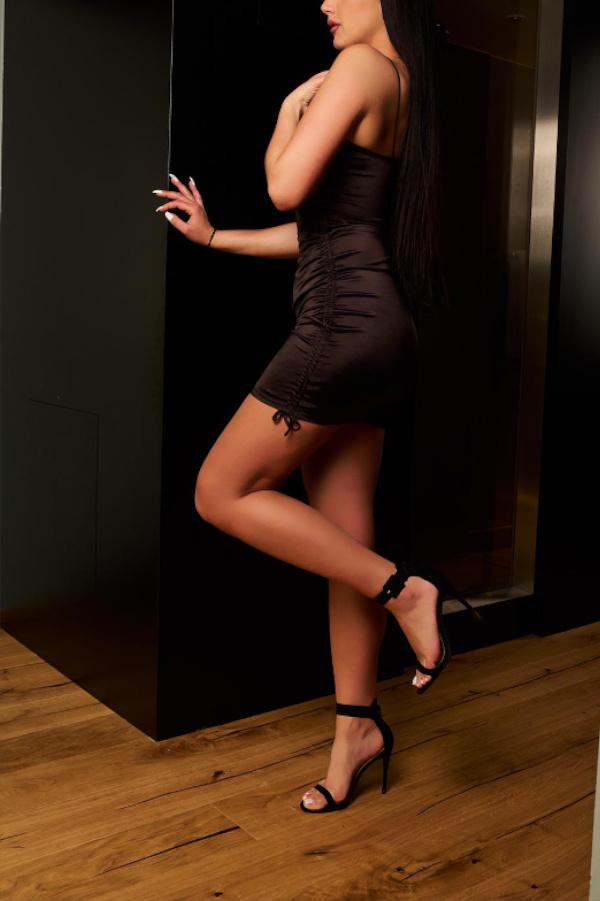 Melanie - Escort Model Frankfurt im engen schwarzen Kleid mit schwarzen High Heels.