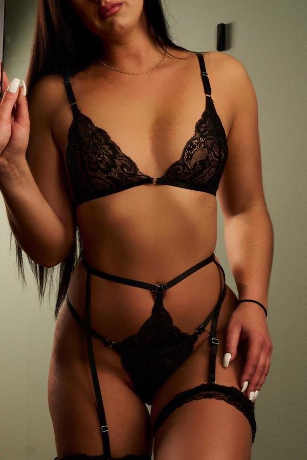 Melanie - Escort Model Frankfurt in schwarzen Dessous vor einer Wand stehend.