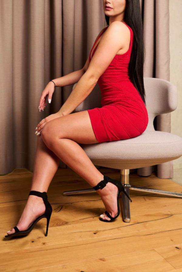 Melanie - Escort Model Frankfurt im roten Kleid auf einem Sessel sitzend.