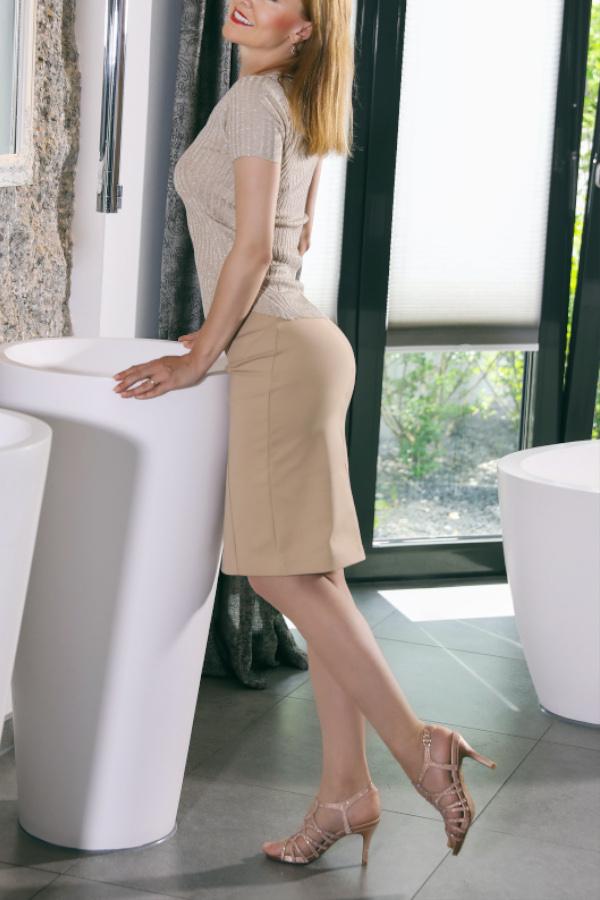 Nicole - Escort Model München in Rock und Top im Badezimmer.