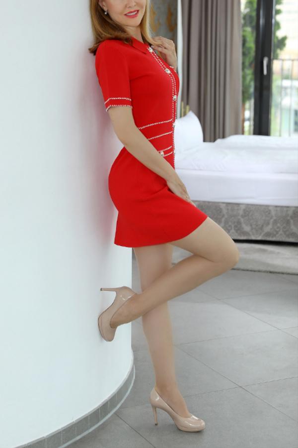Nicole - Escort Model München in roten KLeid an die Wand gelehnt.